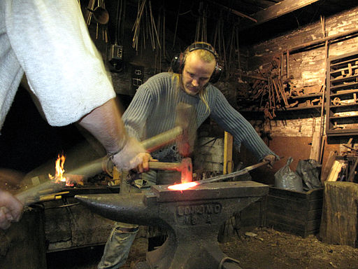 512px-3_tourist_helping_artist_blacksmith_in_finland