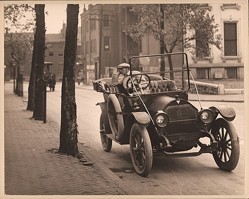 Man_seated_in_automobile_on_unidentified_street